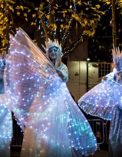 Christmas stilt walking trio led higher beings